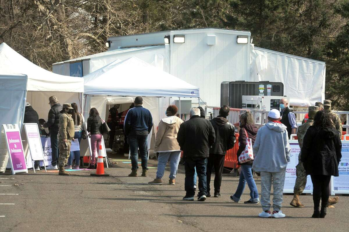 People wait in line for their scheduled COVID-19 vaccination appointments at FEMA's new COVID-19 mobile vaccination unit, which is set up and running this week in parking lot of Connecticut's Beardsley Zoo, in Bridgeport, Conn. March 29, 2021.