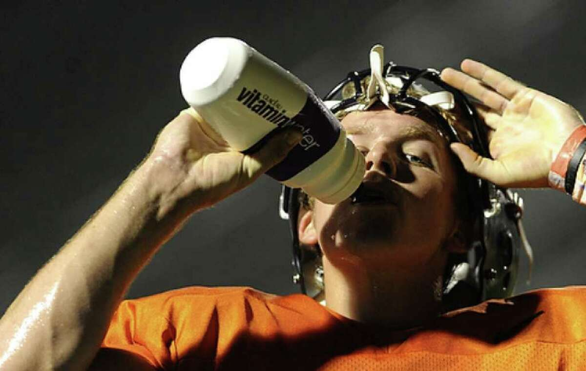 Quarterback Cole Hubble refreshes himself during the UTSA football team's first-ever practice.