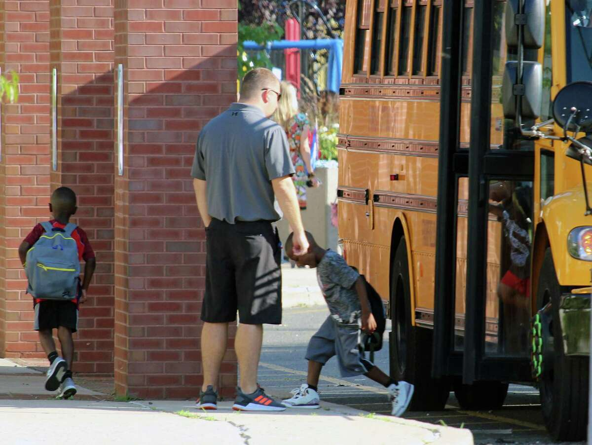File photo of a student heading off the bus and into McKinley Elementary School in Fairfield, Conn.