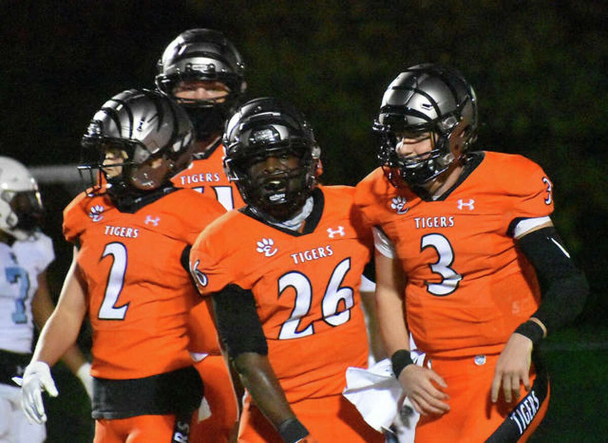 Edwardsville's Justin Johnson Jr. (26) celebrates with teammates Grant Matarelli (2) and Ryan Hampton (3) after Johnson Jr.'s fourth of five touchdowns in the Tigers' SWC victory over Belleville East on Friday night in Edwardsville. The touchdown was Johnson Jr.'s 49th career touchdown, breaking Collin Gardiner's former record of 48 rushing touchdowns.