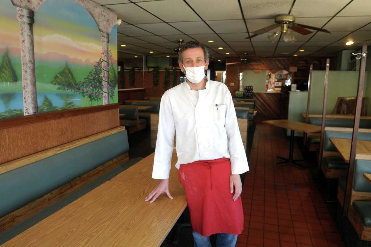 Owner Paul Goncalves poses in the dining room of San Remos Pizza & Restaurant, in Bridgeport, Conn. March 29, 2021.
