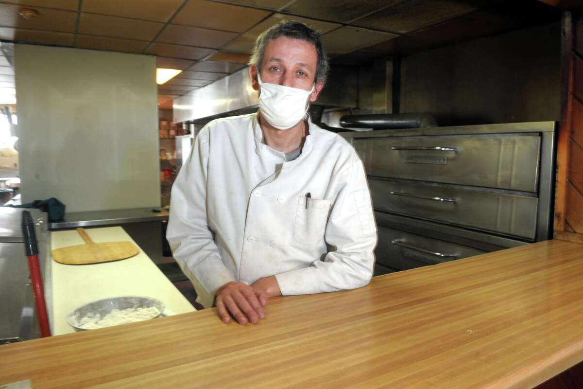 Owner Paul Goncalves poses behind the counter of San Remos Pizza & Restaurant, in Bridgeport, Conn. March 29, 2021.
