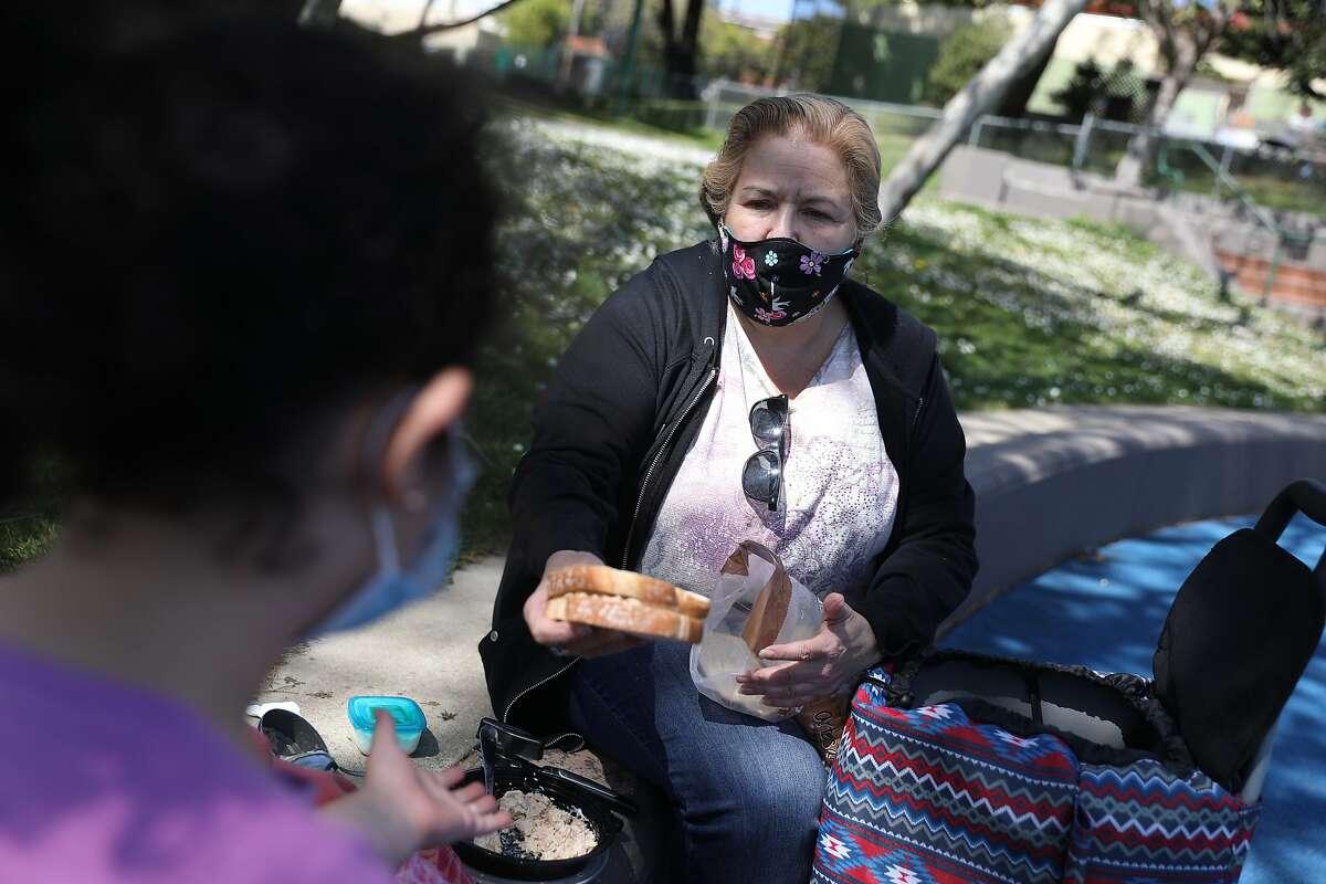 Deborah Carlos offers her granddaughter Myrna a sandwich during an outing at Potrero del Sol park in San Francisco.