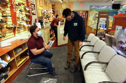 Matt Arciuolo II, helps customer Jonathan Fava at Arciuolo's Shoes in Milford, Conn., on Friday March 26, 2021. The business will be celebrating its 100th anniversary in August.