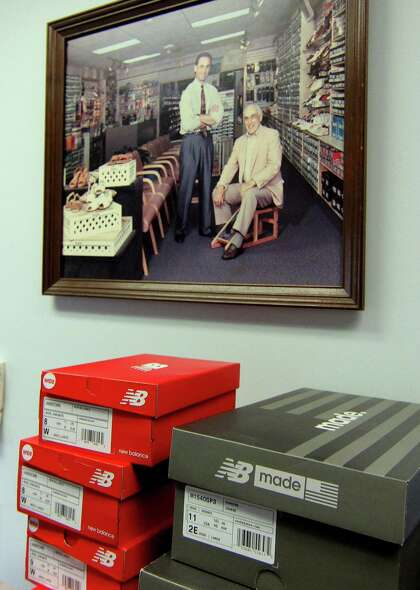 A portrait of Matt Arciuolo Sr. seated, and Matt Arciuolo Jr. hangs on the wall at Arciuolo's Shoes in Milford, Conn., on Friday March 26, 2021. The business will be celebrating its 100th anniversary in August.