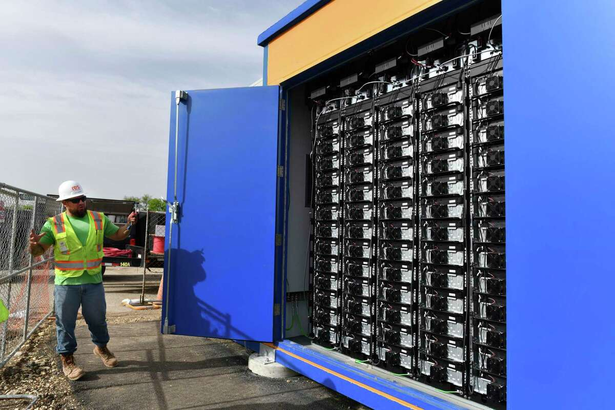 Eric Rivera opens a door to display some of the 403 batteries in one unit that holds solar-generated energy at the CPS Energy solar farm at 9800 West Commerce on Thursday, April 11, 2019.