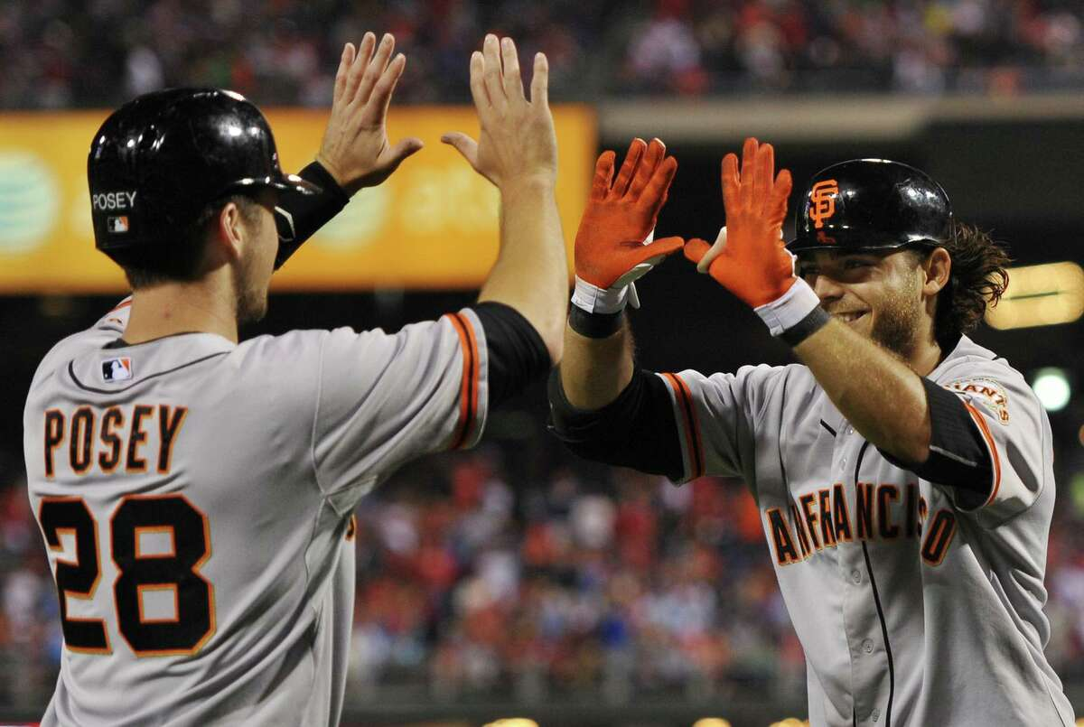 Buster Posey congratulates Giants' teammate Brandon Crawford for his grand slam in a July 2012 game in Philadelphia.