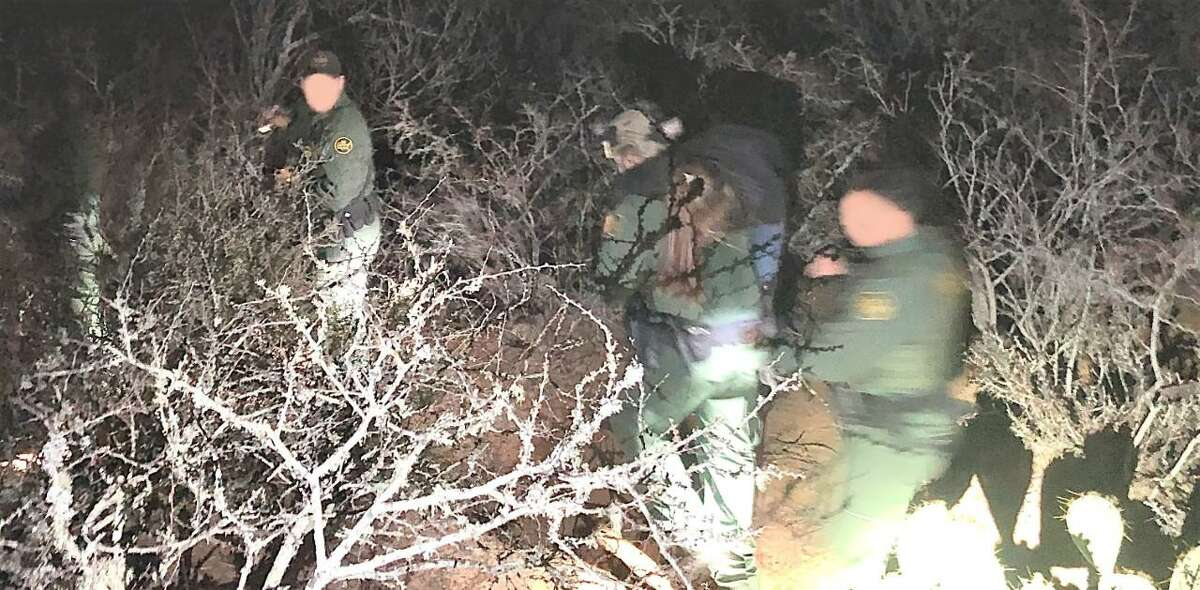 A U.S. Border Patrol agent is seen carrying a woman through the brush. The woman was an immigrant illegally present in the country who was suffering from seizures.