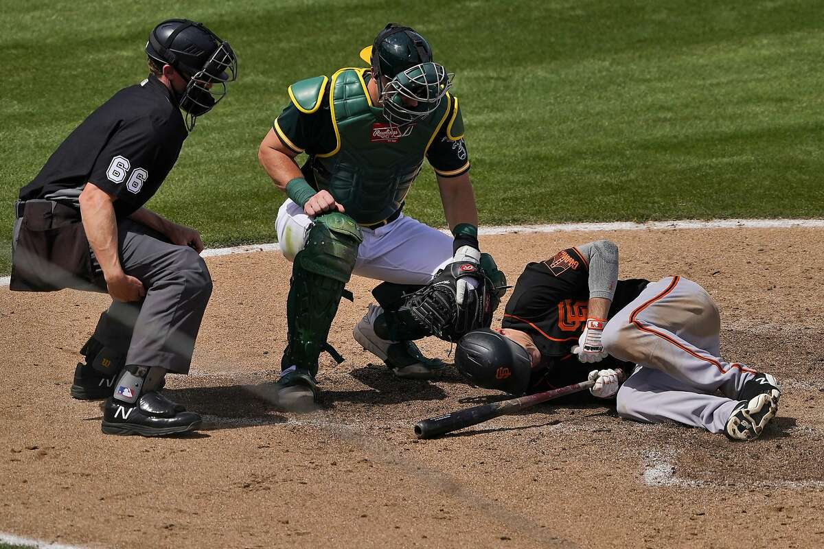 The Giants' Mike Yastrzemski went to the ground after being hit by a pitch during the third inning Monday.