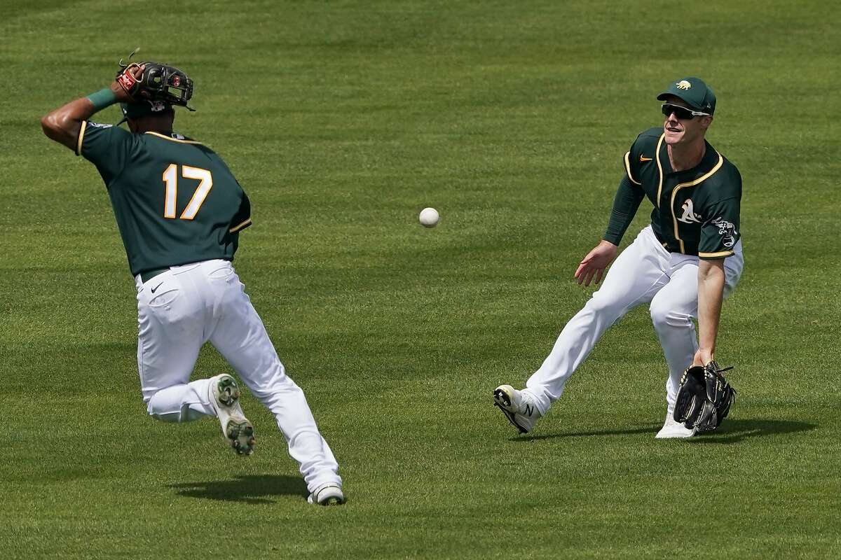 A's shortstop Elvis Andrus (17) and left fielder Mark Canha can't get to a Wilmer Flores bloop in the Giants' victory.