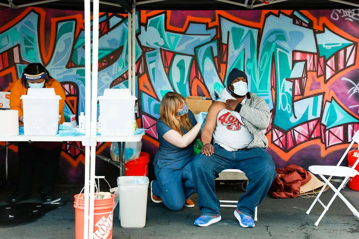 Nurse Tara O'Flaherty (left) prepares to administer the Johnson & Johnson COVID-19 vaccine to Lamar Bush (right) on Thursday, March 11, 2021 in Oakland, California. The Trust Clinic hosted a mass vaccination day for people who are unhoused, housing insecure or staff members of the clinic.