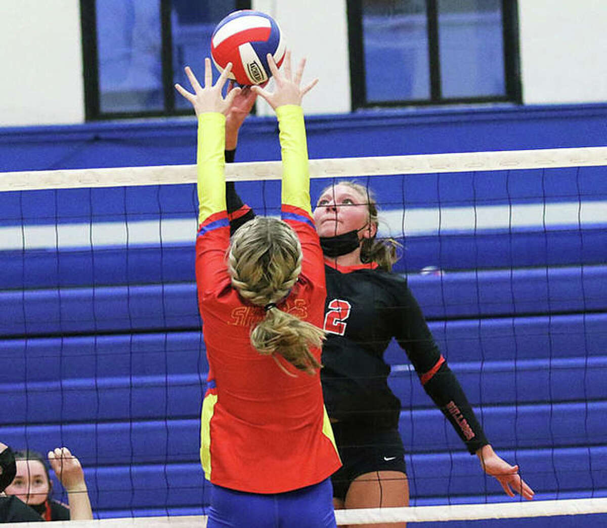 Staunton senior Taryn Russell (2) tips over the block of Roxana's Peyton Petit during a SCC girls volleyball match March 22 at Milazzo Gym in Roxana. Russell had a career-high 14 kills in the Bulldogs' win.