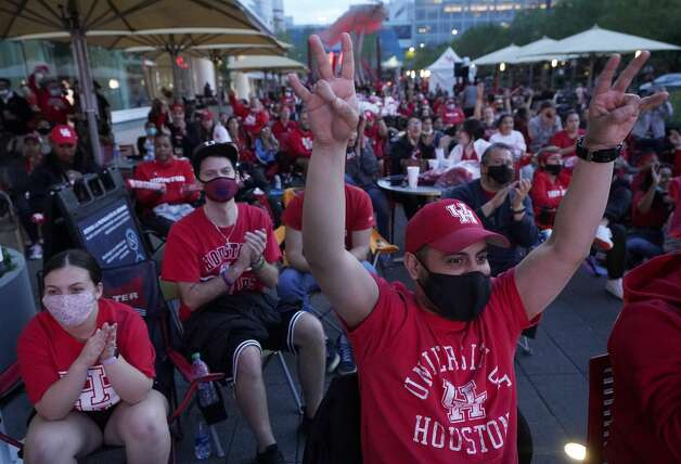 Eder Valencia, right, of Houston and a junior at the University of Houston, cheers during a watch party the UH game on an outdoor screen at Avenida Houston Monday, March 29, 2021 in Houston as UH played against Oregon State in the NCAA Tournament Midwest Region. Photo: Melissa Phillip/Staff Photographer / © 2021 Houston Chronicle