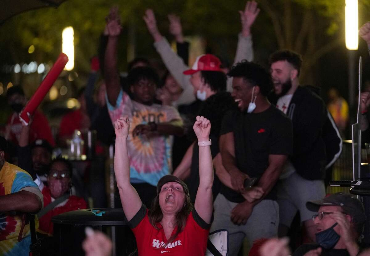 Fans cheers in the final seconds as they watch the University of Houston game on an outdoor screen at Avenida Houston Monday, March 29, 2021 in Houston as UH played against Oregon State in the NCAA Tournament Midwest Region.