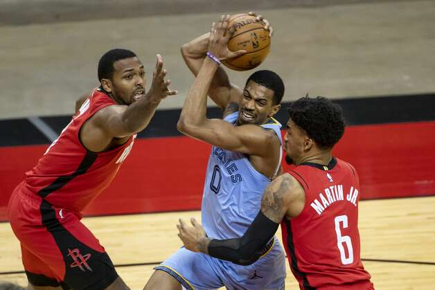 Memphis Grizzlies guard De'Anthony Melton (0) drives through the defense of Houston Rockets forward Sterling Brown (0) and Houston Rockets forward Kenyon Martin Jr. (6) during the third quarter of an NBA game between the Houston Rockets and the Memphis Grizzlies on Monday, March 29, 2021, at Toyota Center in Houston. Photo: Mark Mulligan/Staff Photographer / © 2021 Mark Mulligan / Houston Chronicle