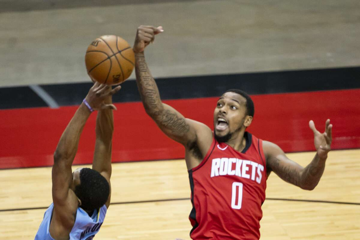 Houston Rockets forward Sterling Brown (0) tries to stop a shot by Memphis Grizzlies guard De'Anthony Melton (0) during the third quarter of an NBA game between the Houston Rockets and the Memphis Grizzlies on Monday, March 29, 2021, at Toyota Center in Houston.
