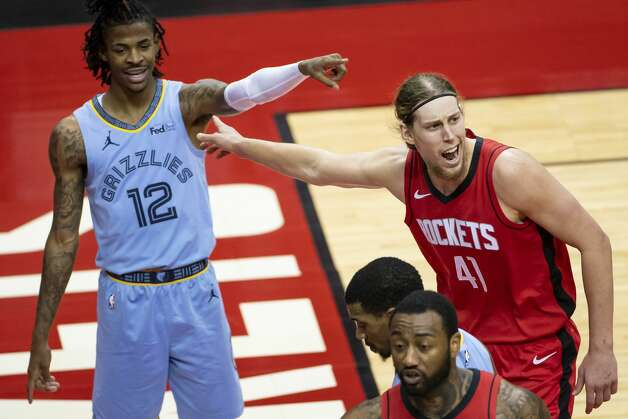 Memphis Grizzlies guard Ja Morant (12) and Houston Rockets forward Kelly Olynyk (41) point at each other saying the ball went out of bounds off of the other one during the second quarter of an NBA game between the Houston Rockets and the Memphis Grizzlies on Monday, March 29, 2021, at Toyota Center in Houston. Photo: Mark Mulligan/Staff Photographer / © 2021 Mark Mulligan / Houston Chronicle