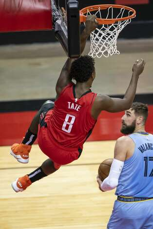 Houston Rockets forward Jae'Sean Tate (8) hangs on the basket above Memphis Grizzlies center Jonas Valanciunas (17) after a dunk during the second quarter of an NBA game between the Houston Rockets and the Memphis Grizzlies on Monday, March 29, 2021, at Toyota Center in Houston. Photo: Mark Mulligan/Staff Photographer / © 2021 Mark Mulligan / Houston Chronicle