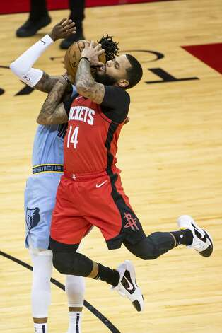 Houston Rockets guard D.J. Augustin (14) draws a foul from Memphis Grizzlies guard Ja Morant (12) during the first quarter of an NBA game between the Houston Rockets and the Memphis Grizzlies on Monday, March 29, 2021, at Toyota Center in Houston. Photo: Mark Mulligan/Staff Photographer / © 2021 Mark Mulligan / Houston Chronicle