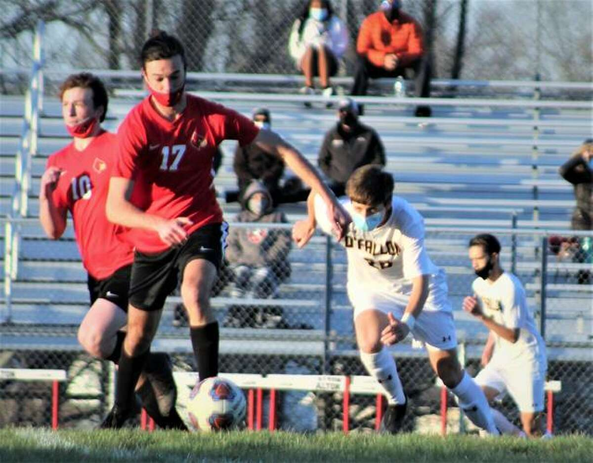 Chase Ely of Alton (17) dribbles upfield and is pursued by O'Fallon's Nolan Kumming (20) Monday at Alton High.