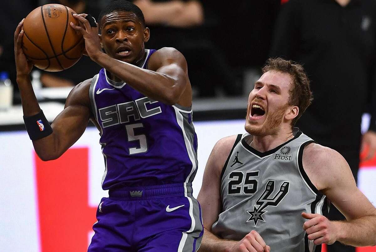 Jakob Poeltl (25) of the San Antonio Spurs screams as De'Aaron Fox of the Sacramento Kings grabs a rebound on Monday.