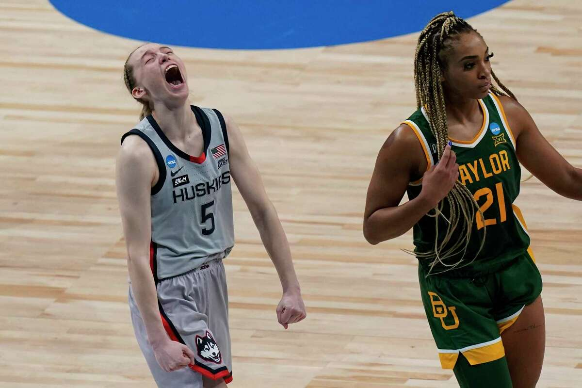 Connecticut's Paige Bueckers, who had 28 points, including 10 in a game-turning 19-0 run, can't hide her excitement while Baylor's DiJonai Carrington was left to lament a last-second play that didn't go her way.