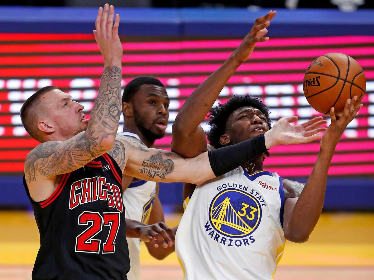 Golden State Warriors' James Wiseman grabs a rebound from Andrew Wiggins and Chicago Bulls' Daniel Theis during 3rd quarter of NBA game at Chase Center in San Francisco, Calif., on Monday, March 29, 2021,