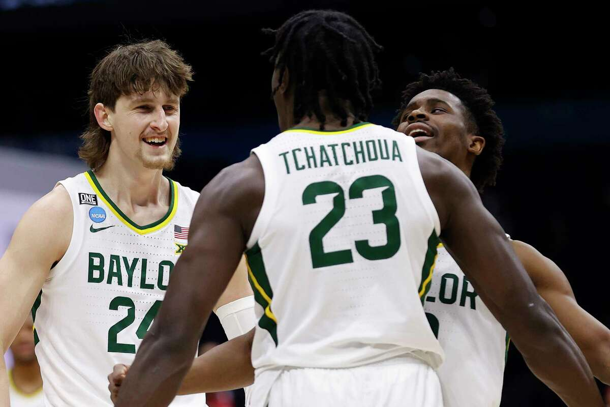 INDIANAPOLIS, INDIANA - MARCH 29: Jonathan Tchamwa Tchatchoua #23 of the Baylor Bears celebrates with Matthew Mayer #24 and Adam Flagler #10 against the Arkansas Razorbacks during the second half in the Elite Eight round of the 2021 NCAA Men's Basketball Tournament at Lucas Oil Stadium on March 29, 2021 in Indianapolis, Indiana.