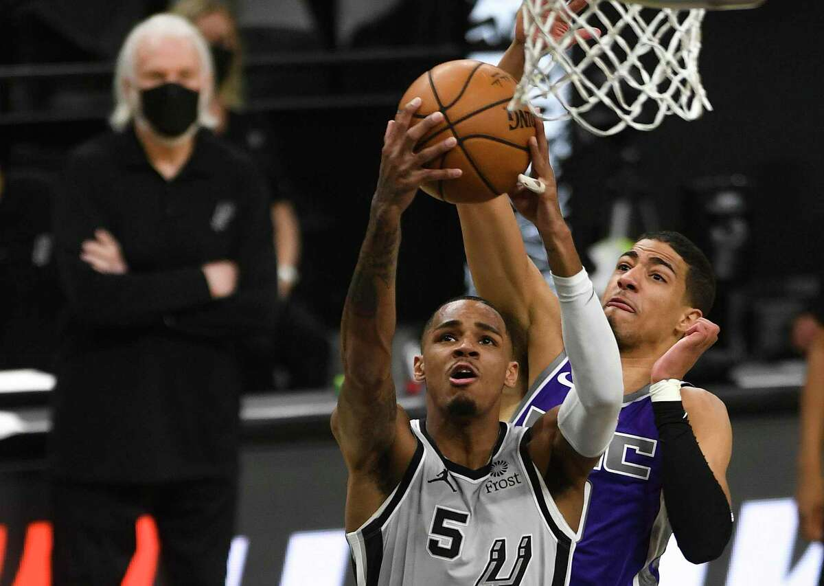 DeJounte Murray shoots and scores against the Sacramento Kings during NBA action in the AT&T Center on Monday, March 29, 2021. Coach Gregg Popovich watches in the background.