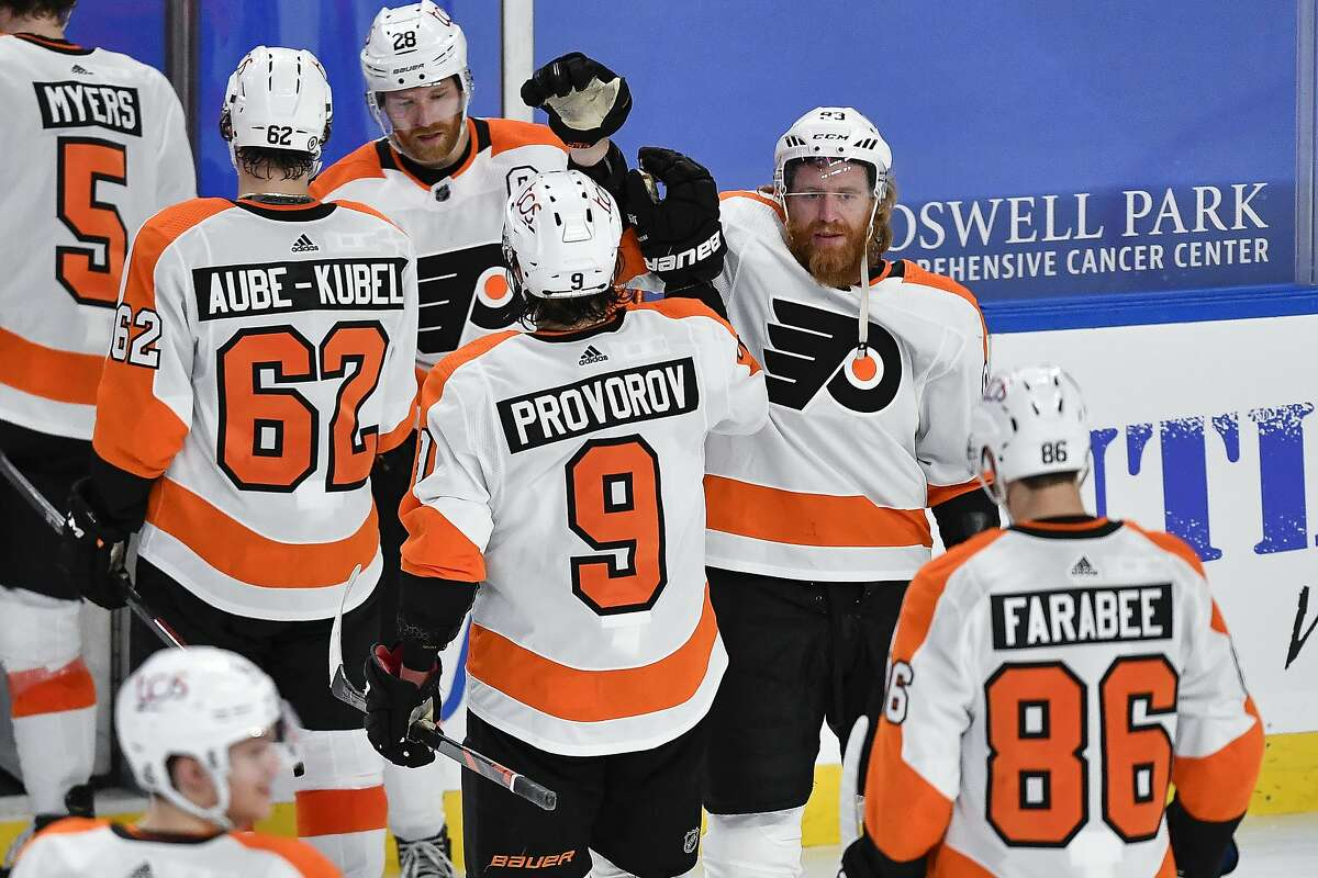 Philadelphia Flyers right wing Jakub Voracek, facing right, congratulates defenseman Ivan Provorov (9) on his winning goal against the Buffalo Sabres in an NHL hockey game in Buffalo, N.Y., Monday, March 29, 2021. (AP Photo/Adrian Kraus)