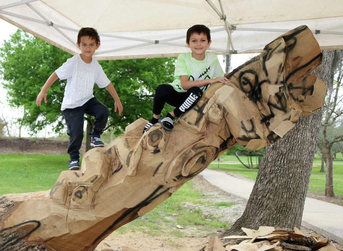 With chainsaw artist James Phillips' encouragement, Owen Liufau, left and his brother Isaac clamber on the sculptor's work in progress at Taylor Lake Village Community Park.