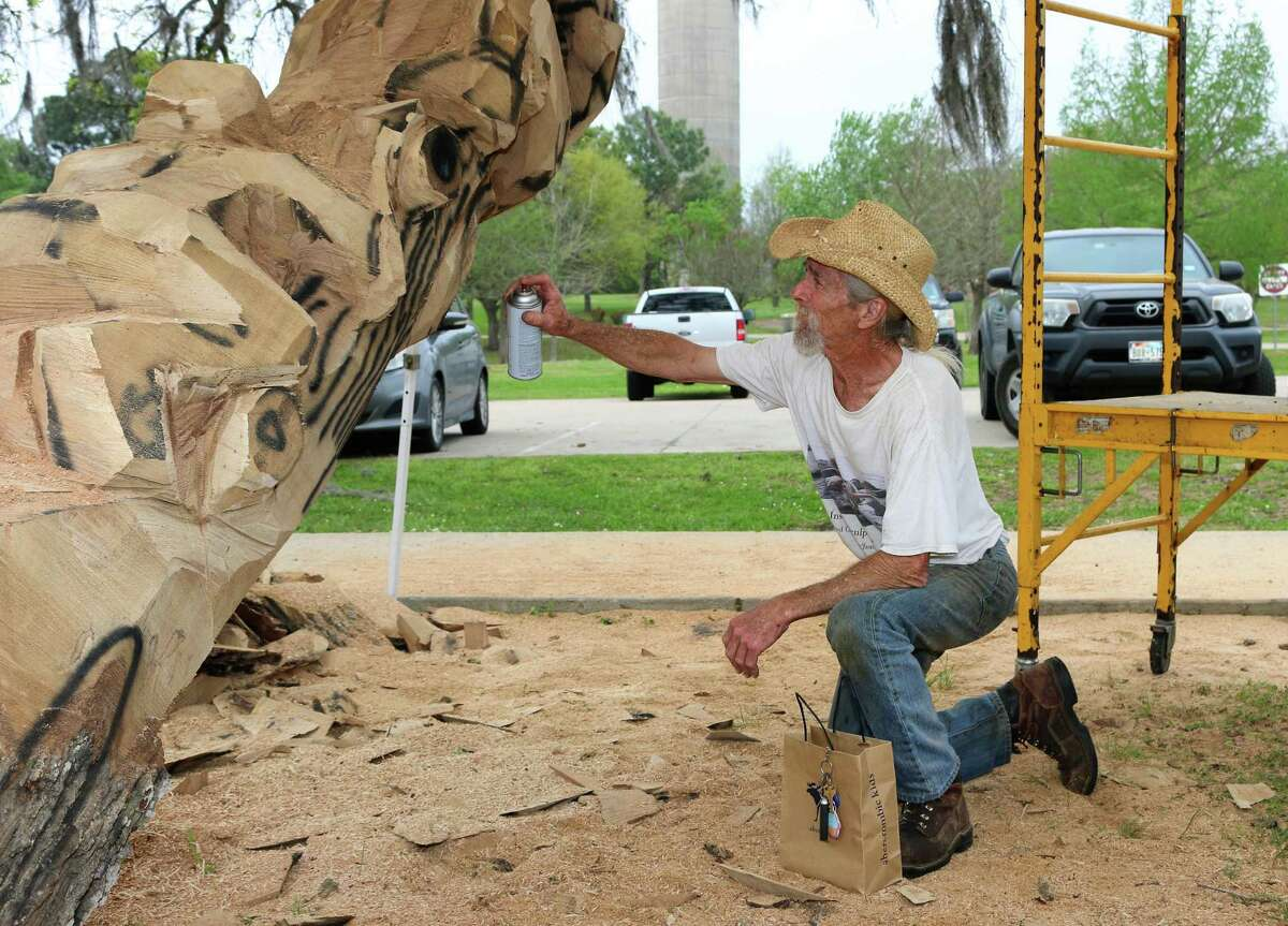 Bay Area resident James Phillips uses spray paint to sketch out the areas he will cut away with a chainsaw in his latest sculpture.