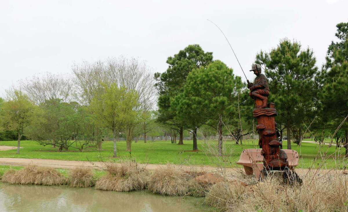 Chainsaw artist James Phillips' sculpture of a boy fishing stands beside a pond at Taylor Lake Village Community Park.