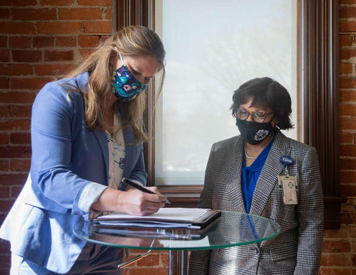 Greenville University President Suzanne Davis signing the partnership agreement as St. John's College of Nursing Chancellor Charlene Aaron looks on.