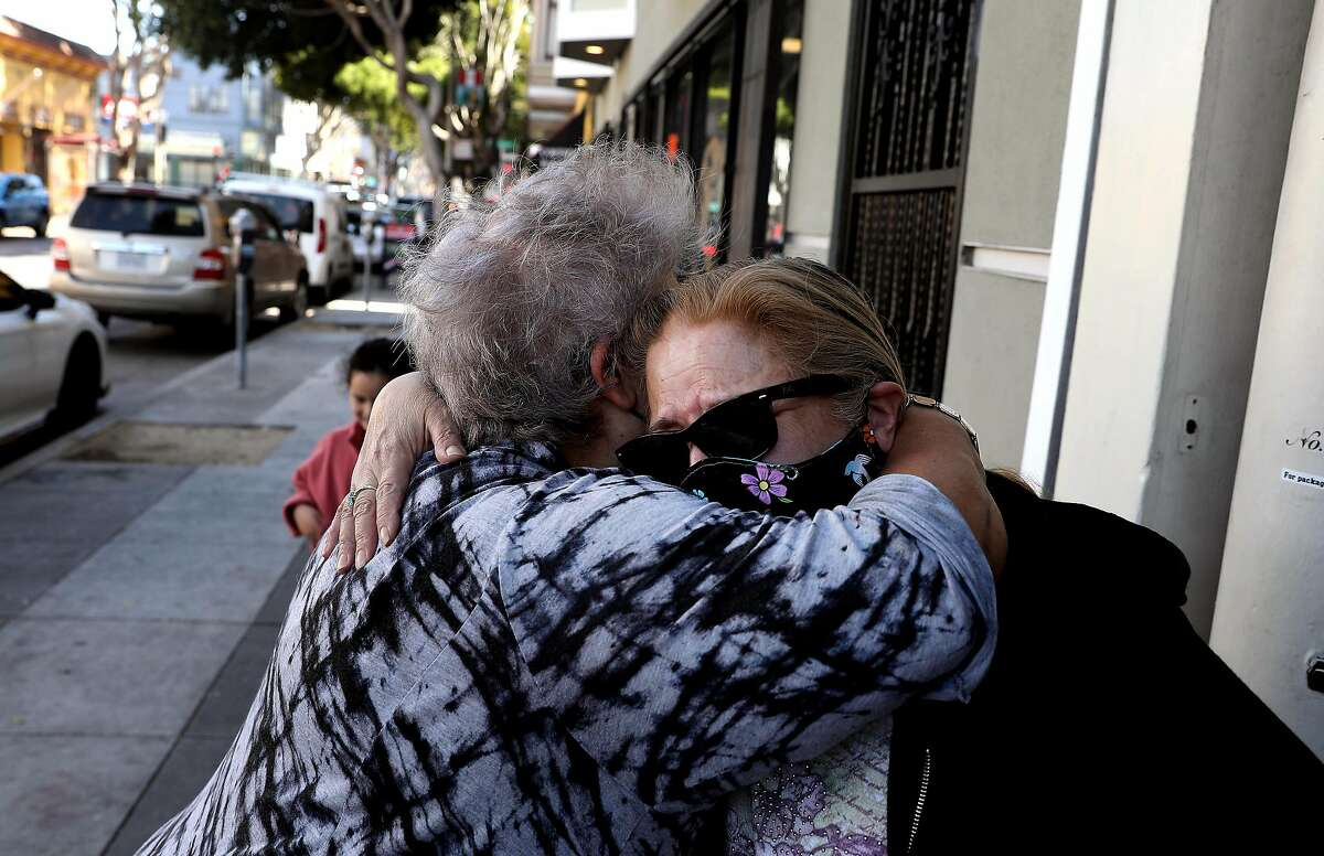 Deborah Carlos (right) is comforted by longtime friend Maria Navarro, over the loss of her mother in January, as they see each other on 24th Street in March. Carlos is taking legal action to fight an Ellis Act eviction and a new bill would limit the ability of property owners to use the Ellis Act to evict tenants.