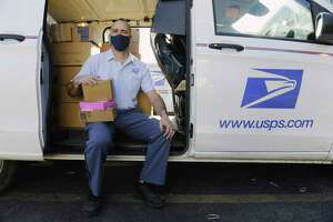 Jeff Clermont, a United States Postal Service letter carrier, poses for a photo at his delivery vehicle before heading out to deliver mail on his route on Tuesday, March 23, 2021, in Albany, N.Y.      (Paul Buckowski/Times Union)
