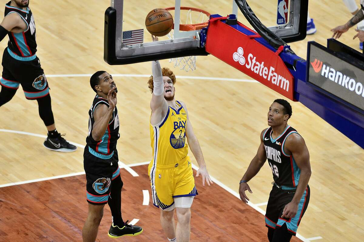 Golden State Warriors guard Nico Mannion shoots between Memphis Grizzlies guards Desmond Bane, right, and De'Anthony Melton in the second half of a March 20 game in Memphis.