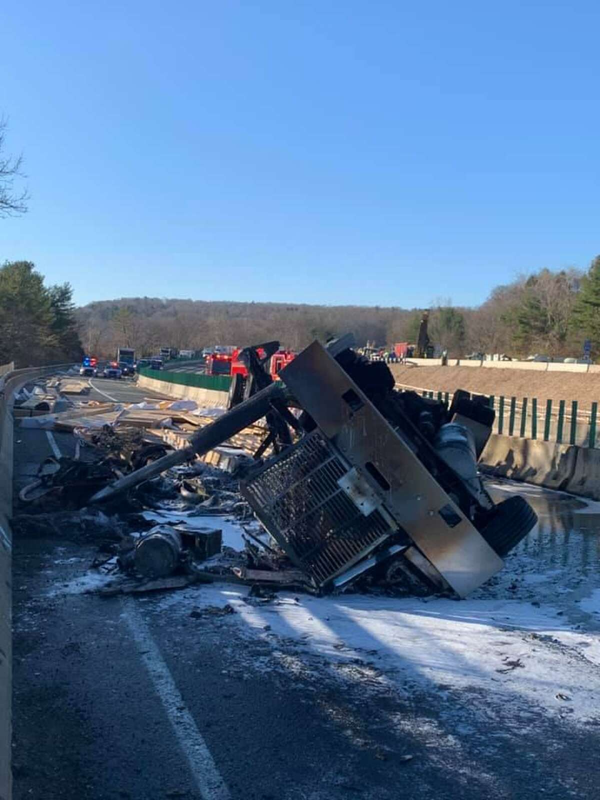 The overturned tractor-trailer on the Rocheambeau Bridge, which is under construction, on Interstate 84 on the Newtown-Southbury line after after firefighters extinguished the blaze Tuesday morning.