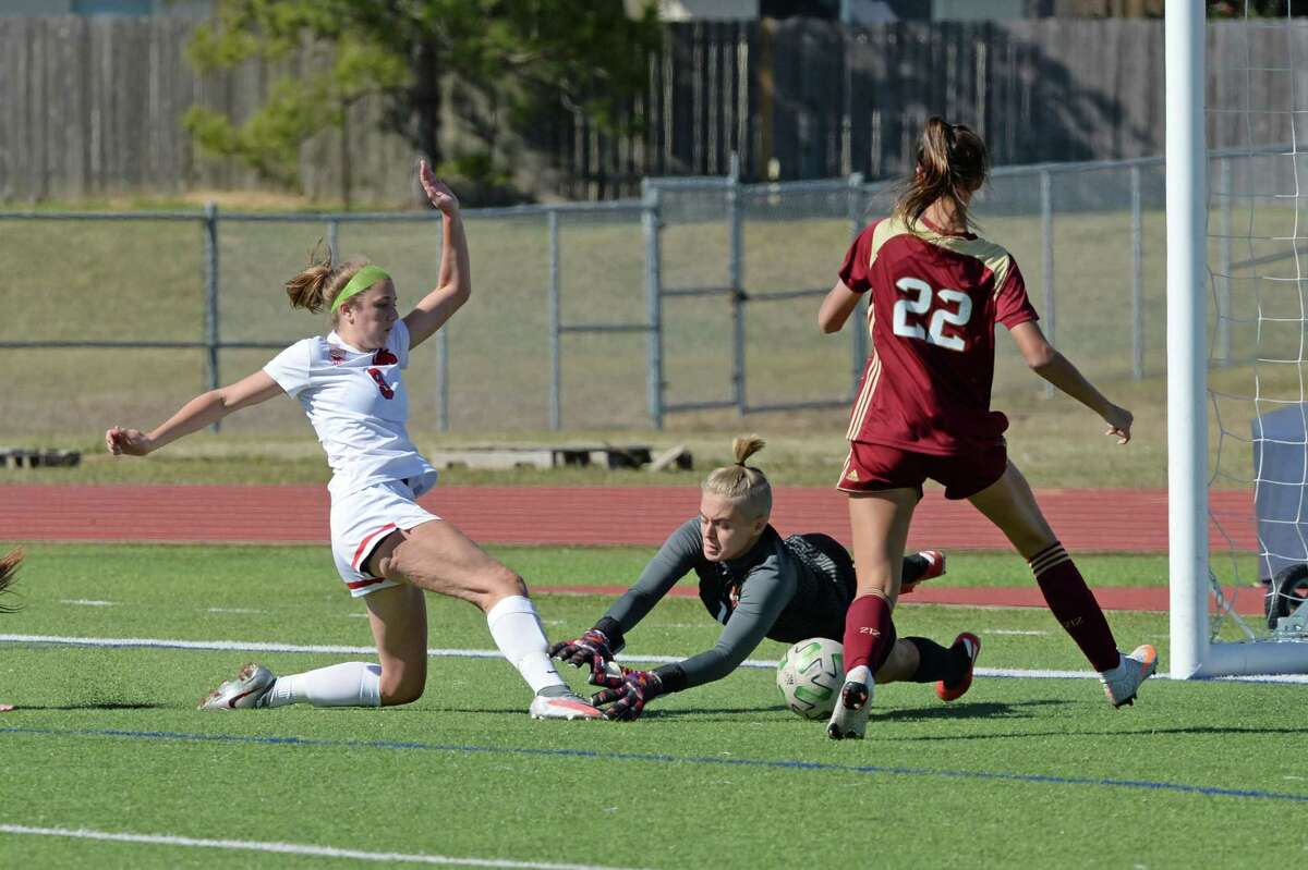 Abby Mohun (9) of Memorial scores a goal past keeper Samantha Nichols (1) of Cy Woods in the second half of the girls soccer game between the Memorial Mustangs and the Cy Woods Wildcats during the I-10 Shootout on Thursday, January 14, 2021 at Tompkins High School, Katy, TX.