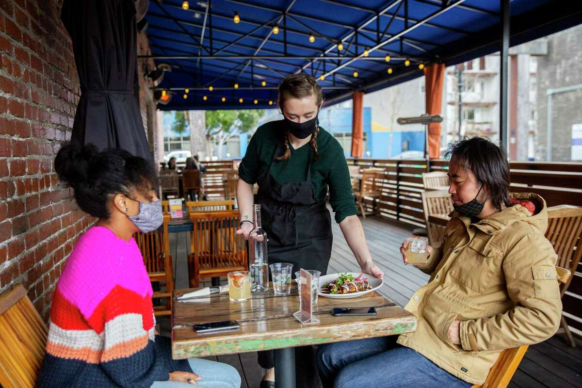 Maddie McGraw serves customers Rachel Kigano (left) and Ryohei Hinokuma at the Calavera patio in Oakland. Alameda County now has moved to the second-least restrictive tier of California's reopening plan, allowing expansion of what activities can occur.
