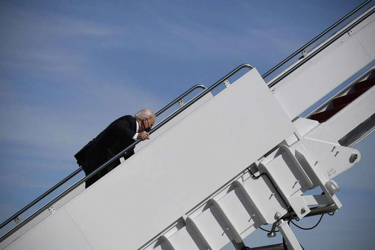 U.S. President Joe Biden trips while boarding Air Force One at Joint Base Andrews in Maryland on March 19, 2021. (Eric Baradat/AFP/Getty Images/TNS)