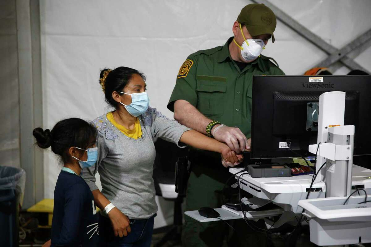 A migrant and her daughter have their biometric data entered at the intake area of the Donna Department of Homeland Security holding facility, the main detention center for unaccompanied children in the Rio Grande Valley, in Donna, Texas, Tuesday, March 30, 2021.