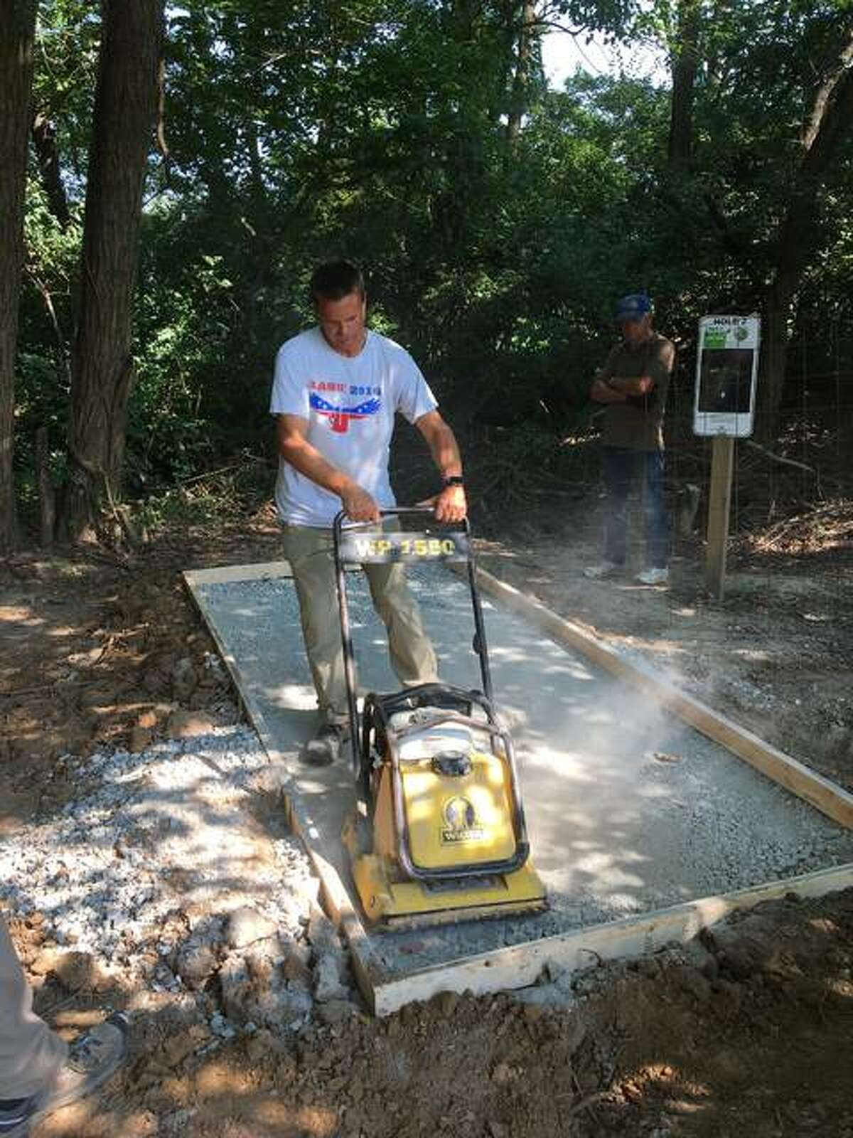 In this August 2020 photo Jason Enos, the owner of Smart Choice Auto in Godfrey, helps prepare a tee box for the La Vista Park Disc Golf Course in Godfrey. The village this week received the Governor's Hometown Award in Economic Opportunities for the project.