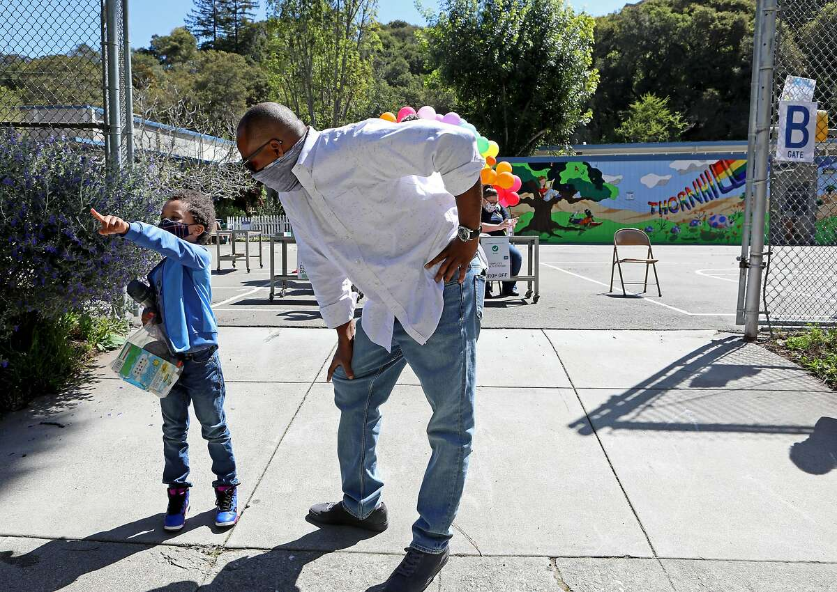 Malchester Brown IV, 6, and his father, Malchester Brown III, rrive for the first day of in-person learning at Thornhill Elementary School in Oakland.