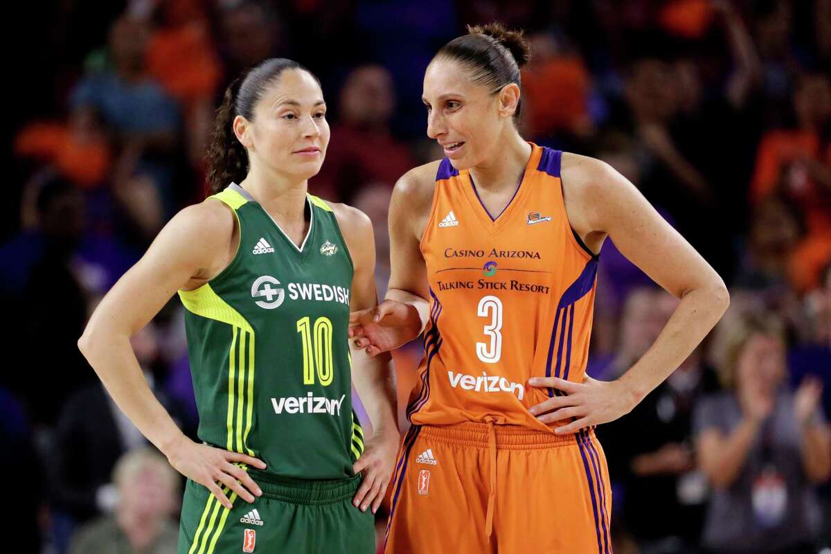 Diana Taurasi talks with Sue Bird during a WNBA basketball game. Both former UConn stars will play in the Olympics this year.