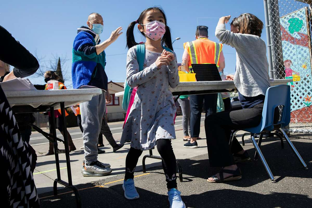 A first grade student arrives for the first day of partial in-person instruction at Garfield Elementary School in Oakland, Calif. Tuesday, March 30, 2021. Garfield Elementary School partially re-opens for students in grades kindergarten through second grade beginning Tuesday, March 30.