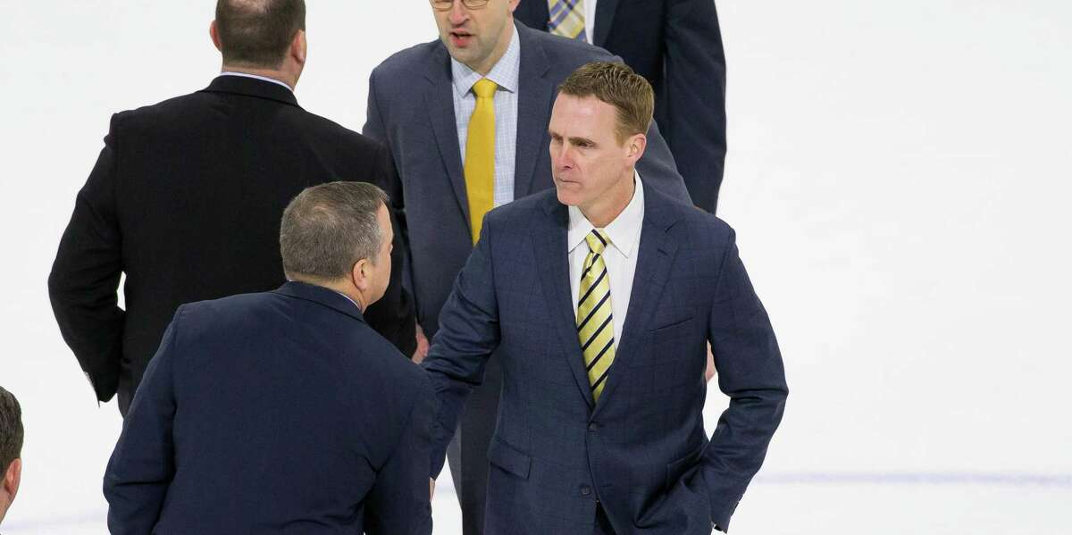 Quinnipiac coach Rand Pecknold shakes hands after a game against Boston University in 2019.