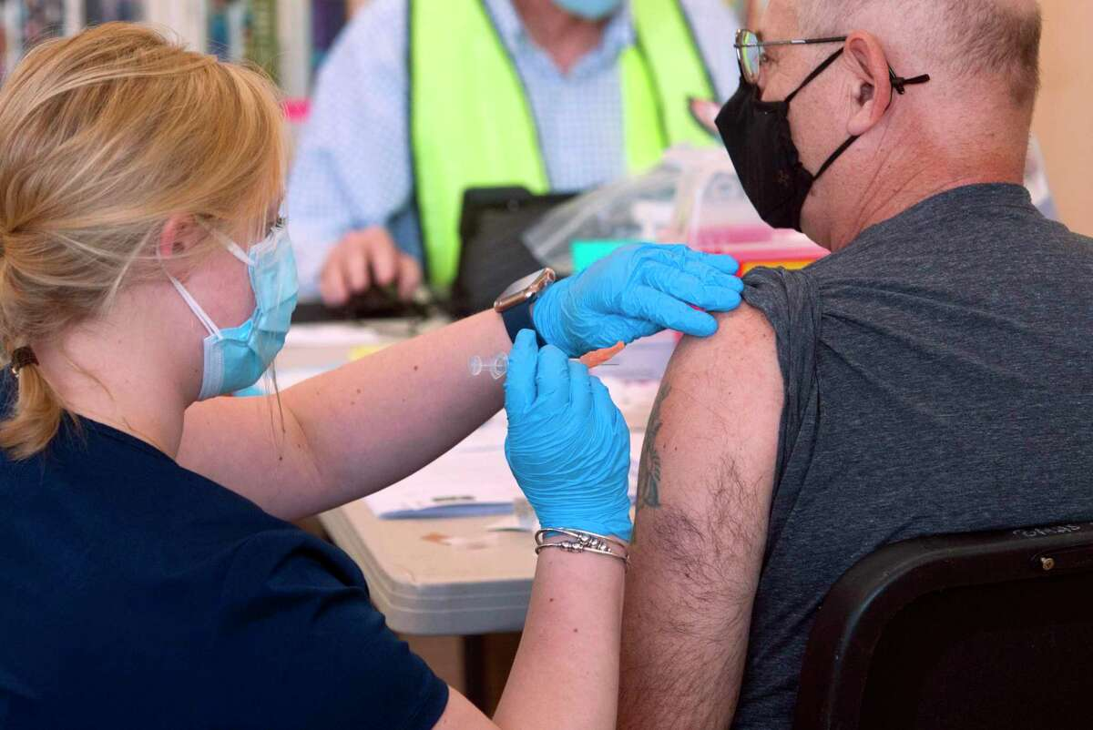 Mallory Bates, an RN at Norwalk Hospital, left, administers a COVID-19 vaccine to Salvatore Rigillo during a Norwalk Health Department mass vaccination clinic for people 45 years and older at Brien McMahon High School in Norwalk, Conn., on Saturday Mar. 20, 2021.