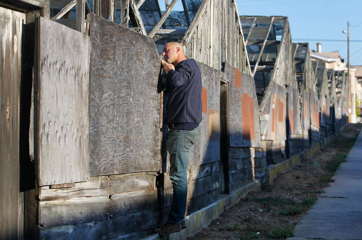 David Gabriner peeks inside a decaying greenhouse in the Portola district of San Francisco in 2015. Gabriner is co-founder of an organization that is hoping to acquire the property and restore the site.