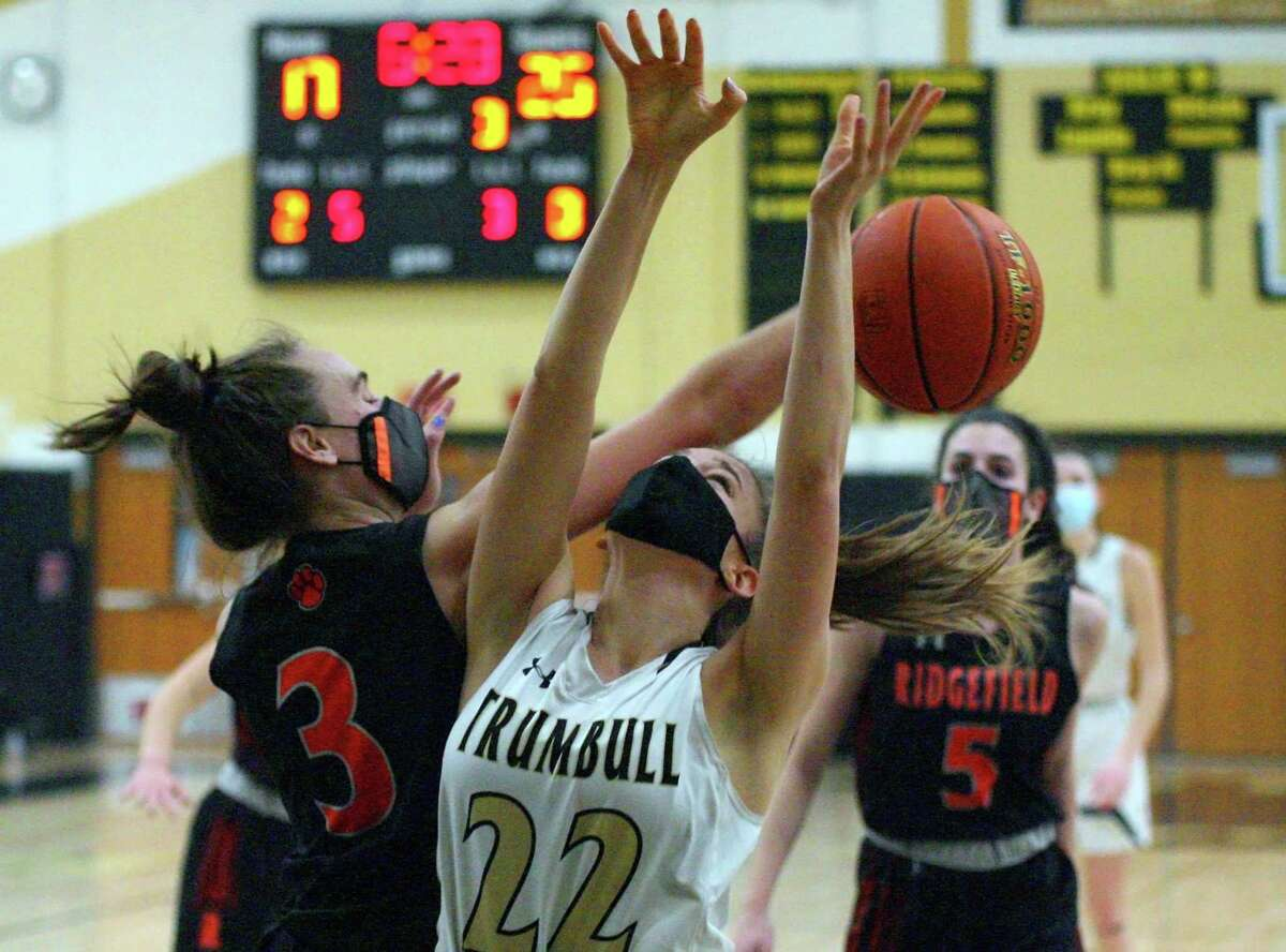 Ridgefied's Kelly Chittenden (3) knocks the ball away from Trumbull's Julia Lindwall as she attempts a shot during girls basketball action in Trumbull, Conn., on Wednesday Feb.10, 2021.